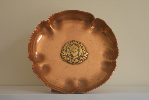 A copper dish with an Ambulance Column badge in the centre
