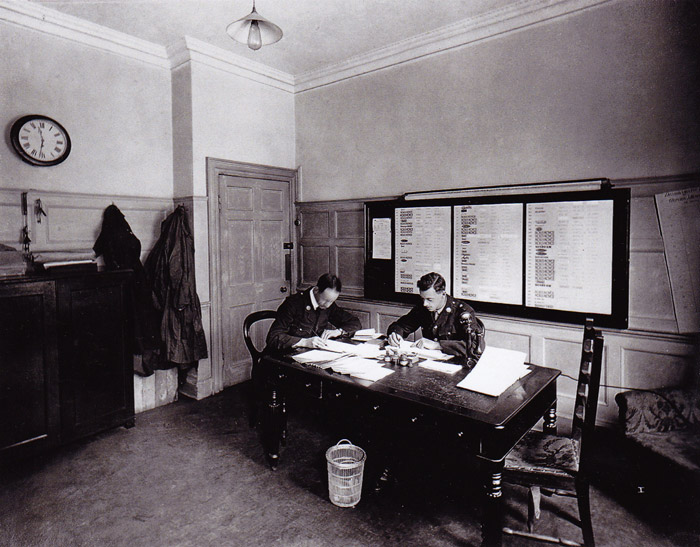 The Petrol Room with two officials working at tables. Messrs Cooper and Strakes.