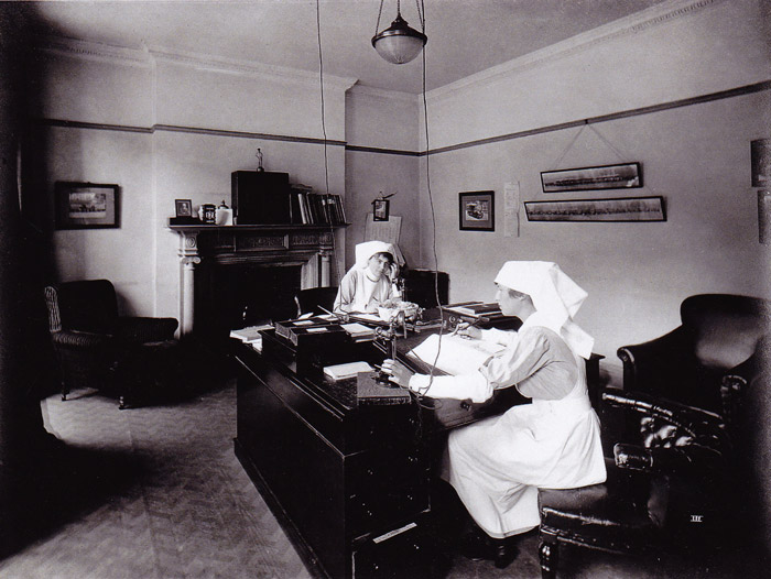 The Record Room, with two women answering the telephone and writing in registers. Mrs Glover (Quartermaster) and Miss Moore.