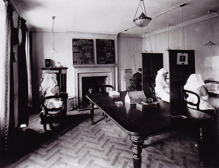 Telephone room, with officials in telephone booths, perhaps answering enquiries Byron II, Davis III, Hall and Mrs Glover (sic).